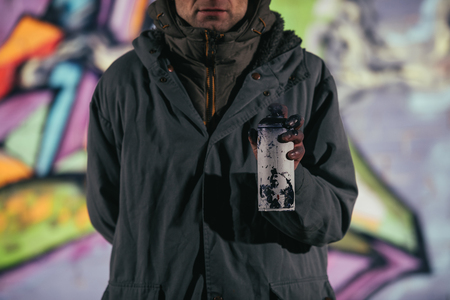 cropped view of man holding can with aerosol paint at night Фото со стока