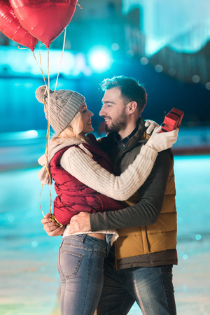 happy young couple with gift box and heart shaped balloons looking at each other on skating rink Banque d'images - 104554314