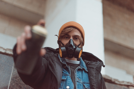 selective focus of man in respirator holding can with spray paint