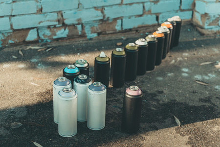 cans with aerosol paint standing in row on asphalt Stok Fotoğraf