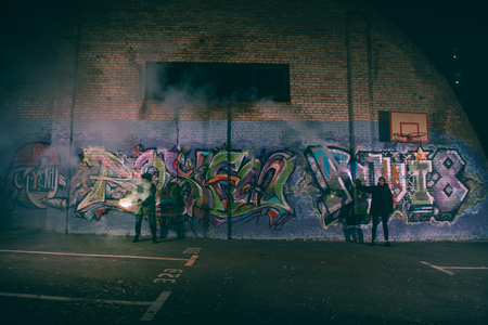 people holding smoke bombs and standing against wall with graffiti at night Stock Photo