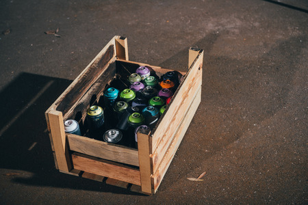 cans with aerosol paint in wooden box