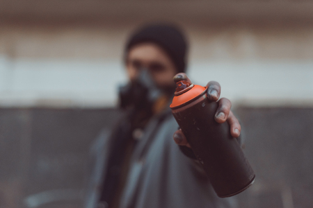 selective focus of street artist in respirator holding can with spray paint 스톡 콘텐츠