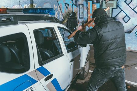 vandal crashing police car with baseball bat while another man painting graffiti on wall