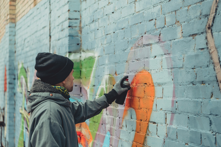 male street artist painting colorful graffiti on wall