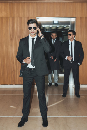 bodyguards waiting for businessman going out from elevator