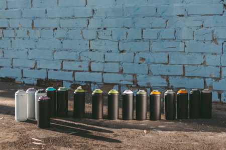 cans with colorful spray paint standing in row on asphalt Reklamní fotografie