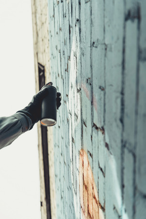 bottom view of man painting colorful graffiti on wall