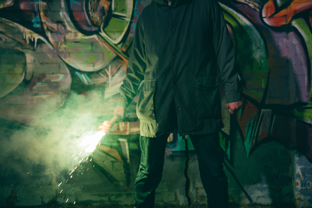 cropped view of man holding smoke bomb and standing against wall with graffiti at night Stock Photo