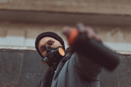 selective focus of street artist in respirator holding can with spray paint 写真素材