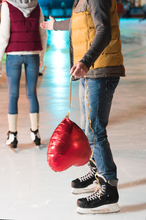 partial view of young man holding heart shaped balloon while girlfriend going away on rink Foto de archivo - 104554366