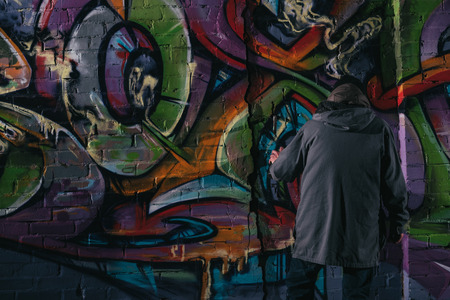 back view of street artist painting graffiti with aerosol paint on wall at night Stock Photo