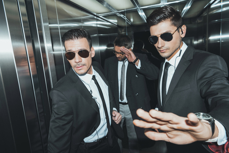 bodyguard stopping paparazzi when celebrity standing in elevator Banco de Imagens