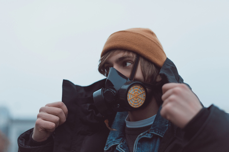 portrait of young man in respirator and hat