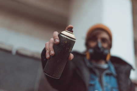 selective focus of street artist in respirator holding can with spray paint Banco de Imagens
