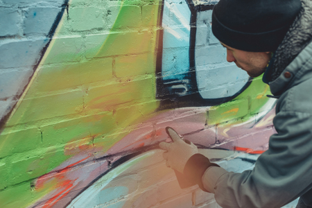 man painting colorful graffiti on wall
