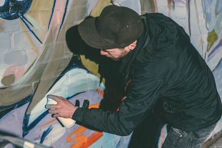 street artist painting colorful graffiti on wall of building at night 写真素材