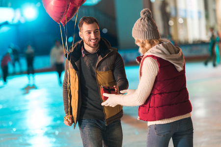 happy young man with balloons presenting gift box to girlfriend at st valentines day on rink Banque d'images - 104554812