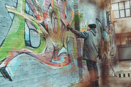 street artist painting colorful graffiti on wall Stock Photo