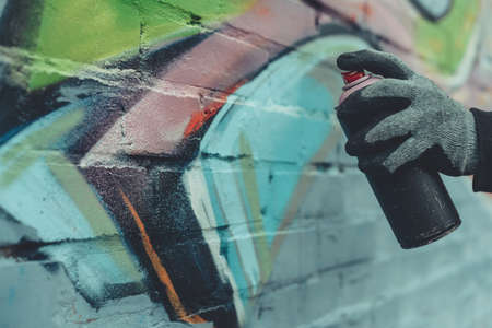 cropped view of man painting colorful graffiti on wall Stockfoto - 104554826