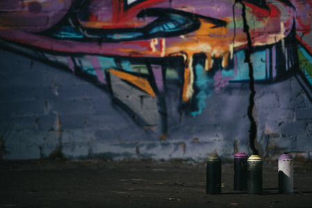 colorful graffiti on wall cans with aerosol paint standing on foreground Stock Photo