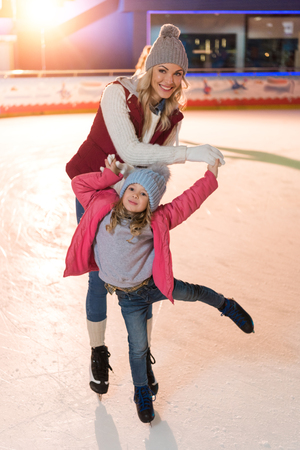 beautiful happy father and daughter smiling at camera while skating on rink