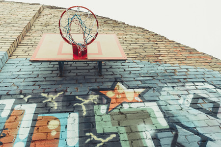 bottom view of basketball hoop on wall with colorful graffiti