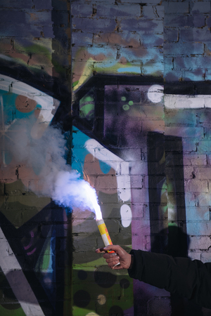 cropped view of hand with smoke bomb against wall with graffiti at night Stock Photo