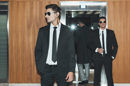 two bodyguards in sunglasses waiting for businessman at elevator