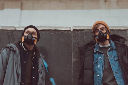 street artists in respirators standing at wall 写真素材