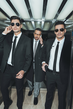 businessman talking by smartphone and going with bodyguards Stock Photo