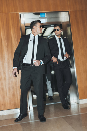 bodyguards reviewing territory when going out from elevator with businessman Stock Photo