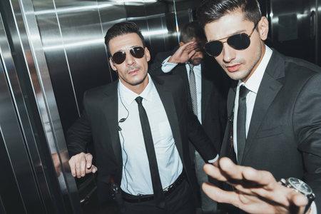 Guardaespaldas parando paparazzi y celebridad cubriendo la cara con la mano en el ascensor
