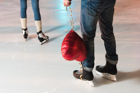 cropped shot of young man holding heart shaped balloon while girlfriend going away on rink Banque d'images - 104554791