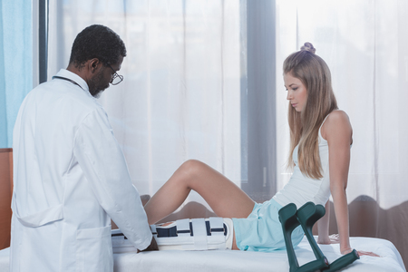 african american doctor putting on leg brace on injured patient leg Stock Photo