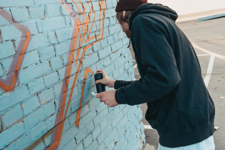 street artist painting colorful graffiti on wall of building