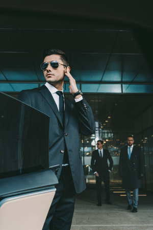 bodyguard opening car door for businessman and listening security earpiece Stock Photo