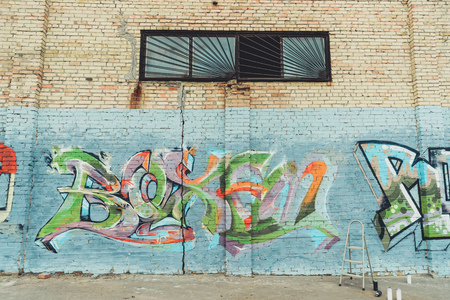cans with spray paint and ladder near colorful graffiti on wall of building in city Stockfoto