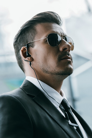 portrait of handsome security guard in sunglasses and security earpiece Stock Photo