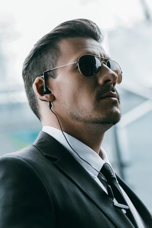 portrait of handsome security guard in sunglasses and security earpiece Reklamní fotografie