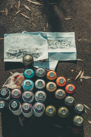 top view of graffiti sketches and cans with colorful spray painton asphalt