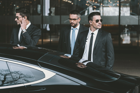 bodyguards going with businessman and reviewing territory near car 版權商用圖片