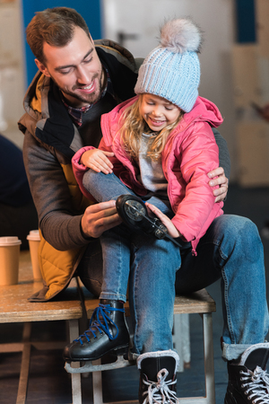 happy father and daughter wearing skates before ice skating