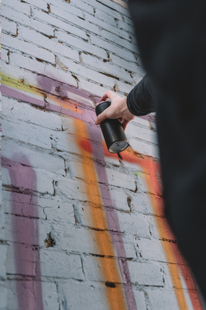 cropped view of street artist painting colorful graffiti on wall of building Фото со стока