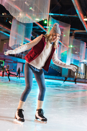 excited beautiful young woman ice skating on rink 版權商用圖片