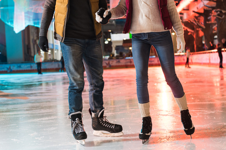 cropped shot of young couple in skates holding hands and ice skating on rink