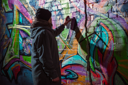 street artist painting graffiti with aerosol paint on wall at night