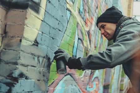 male street artist painting colorful graffiti on wall