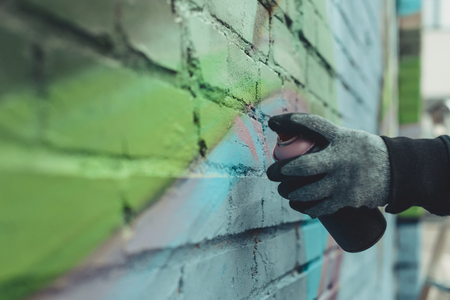 cropped view of man painting colorful graffiti on wall