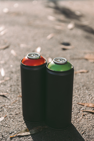 cans with red and green aerosol paint for graffiti on asphalt Stok Fotoğraf